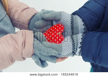 Valentine's Day and love concept. Heart in the hands. Man and woman hands in gloves holding heart close up on winter background. Hands holding red heart outdoor