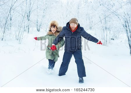 Happy smiling couple running through snow in winter outdoor. Winter love story. People, season, leisure and love concept. People having fun in winter day. Loving couple emotionally running in winter