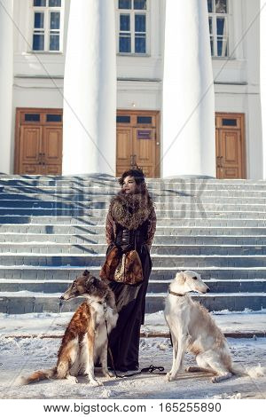 Girl in fur clothes posing with two dogs on a background of a winter snow