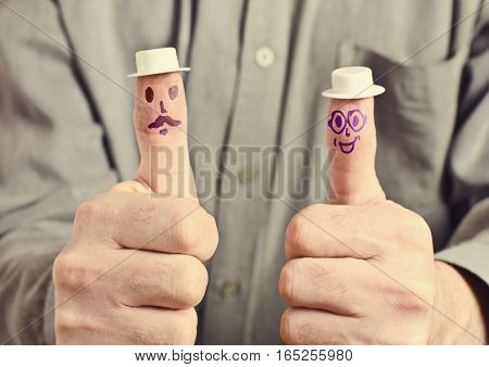 Hand with a raised thumb. Finger painted eyes and mouth wearing a toy hat