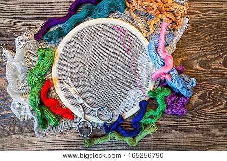 Embroidery. Sewing accessories. Canvas, hoop, thread mouline. Wooden background.