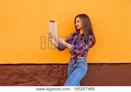 beautiful stylish smiling women make selfie by tablet . Orange background. Copy-space. Outdoor