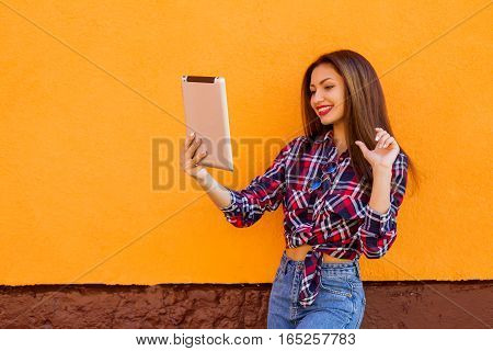beautiful stylish smiling women make selfie by tablet . Orange background. Copy-space.