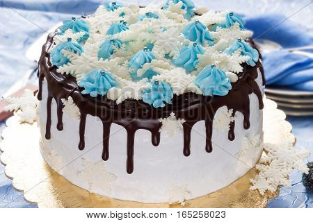 Beautiful cream cake decorated with chocolate leaks cream and sugar snowflakes from mastic