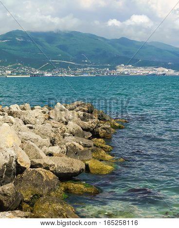 Jutting into the sea from the breakwater mound of stones. The black sea city of Novorossiysk