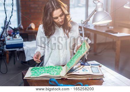 Pretty female tailor choosing a fabric in cloths catalog in studio.