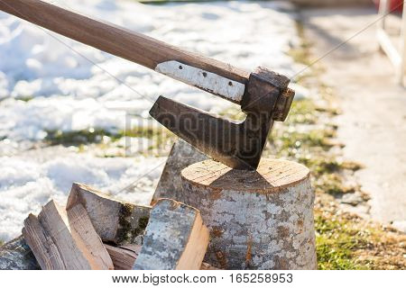 Axe stabbed in the firewood in the front yard