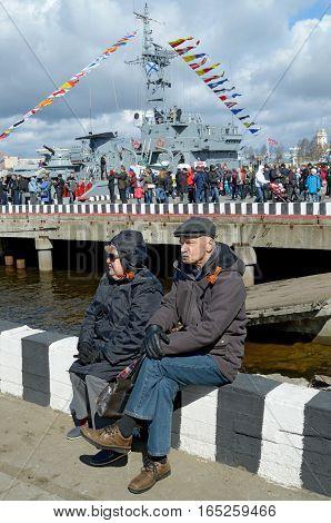 25.04.2015.Russia.Saint-Petersburg.Elderly couple sitting on the pier.On the street the warm sun.