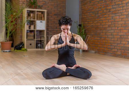 Woman doing yoga meditating in full lotus pose with hands in Namaste in studio.