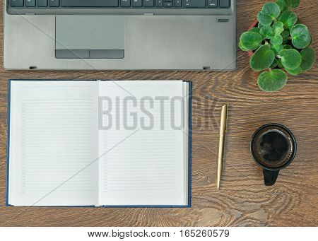 Notebook with pen laptop and flower on a wooden table. Office workplace.