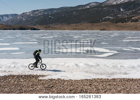 Man on BMX rides on the frozen lake, near the ice.