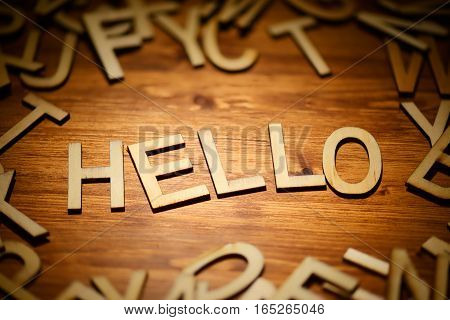 Words Hello written hand made style letters type on a dark wooden background