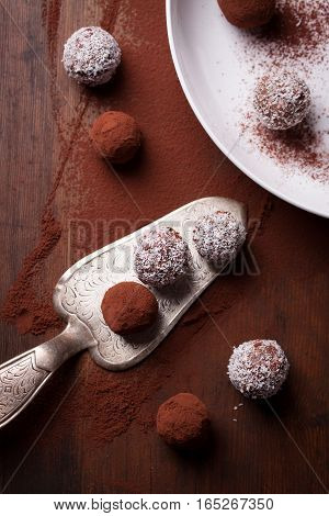 Chocolate sweets with cocoa and coconut chips on a white plate