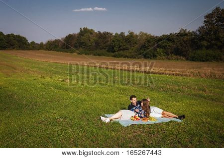 happy couple at a picnic on the meadow