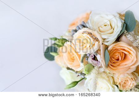 Wedding rings lie on the Bridal bouquet of roses. Gold wedding rings luxary