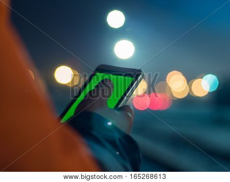 male hands using modern smartphone at night, bokeh light in blurred background, social network concept, night lights