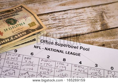 Office Superbowl Pool grid with money on a wooden table