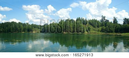 Summer nature landscape panorama with trees on forest lake