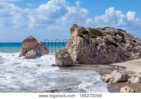 Aphrodite's Rock in Cyprus. Taken on a bright summer's day with rough seas and has some people on the beach giving scale.