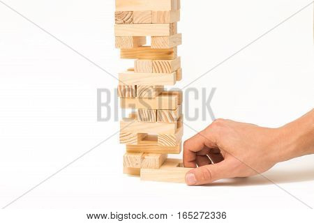 Tower of wooden blocks and man's hand take one block. Isolated on white background.