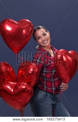 Beautiful smiling woman posing with red heart shaped balloons.