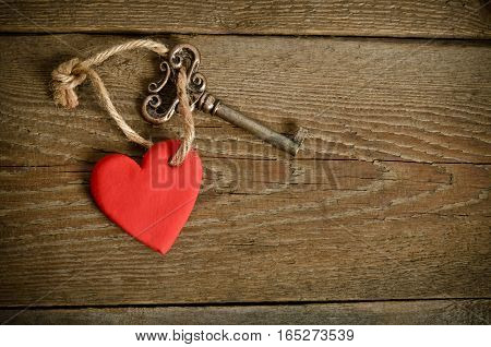 Handmade Heart with key together relating on a wooden board.top view