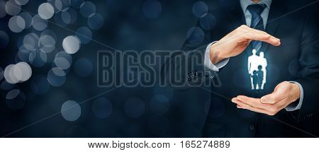 Family life insurance, family services and supporting families concepts. Businessman with protective gesture and silhouette representing young insured family. Right wide banner composition with bokeh in background