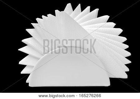 Paper napkins folded like a fan in a glass stand on a black background