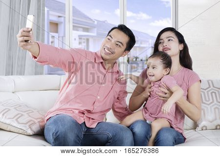 Group of happy Asian family sitting on the couch and taking selfie photo together shot at home