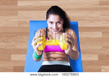 Portrait of indian woman holding a dumbbell while doing sit up on the mattress