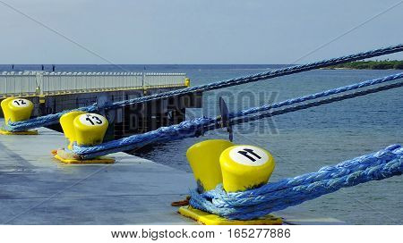 Blue Mooring Lines from Cruise Ship on Yellow Bitts at Pier