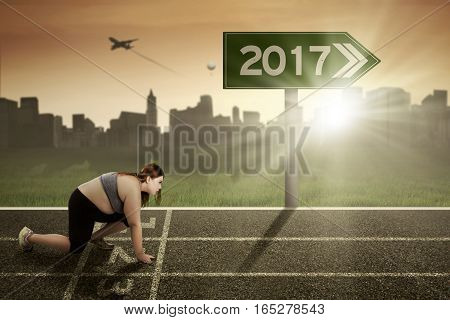 Blonde woman with overweight body wearing sportswear and ready to run on the track with number 2017 on the signpost