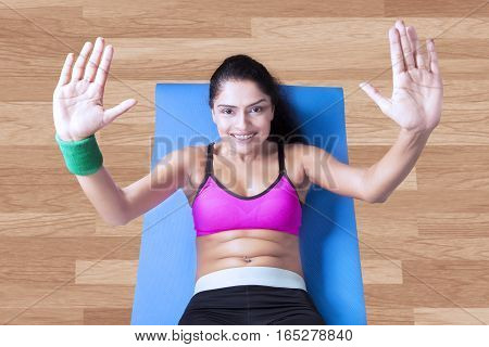 Portrait of young woman doing sit up on the mattress while smiling at the camera