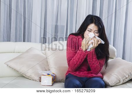 Portrait of young woman wearing warm clothes sneezing in tissue while sitting on sofa