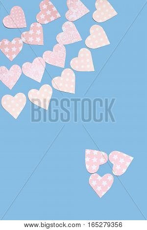 Garlands of tender pink hearts carved by hand from paper with various ornaments on a blue background. Festive background to Valentines Day with empty space for text