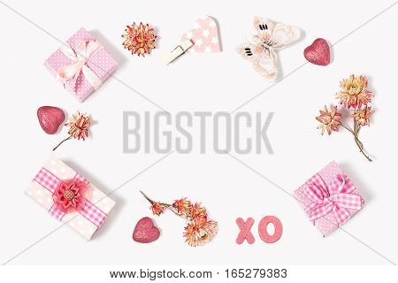 Composition to Valentines Day: gift boxes with bows butterfly flowers little hearts XO letters denoting kisses and hugs. All gifts pink. The mood of love and tenderness. Flat lay top view