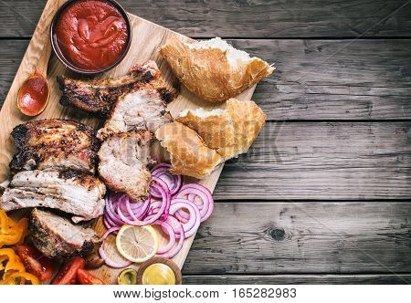 Sliced grilled pork with vegetables on wooden board top view with copy space