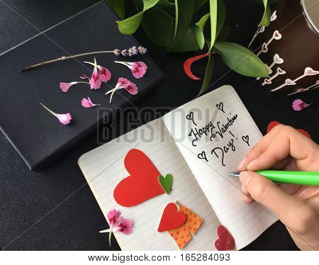 Happy Valentine's Day words written on notebook next to coffee mug with hearts and box with paper hearts and flower petals to decorate present hand holding pen for social image greeting message or promotion