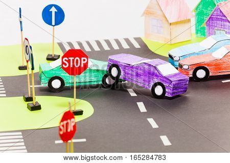 Road accident on a crossings with two handmade paper cars at the toy city