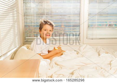 Side view portrait of little boy holding a glass with orange juice sitting in his bed