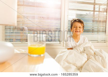 Happy smiling boy starting morning with a glass of orange juice sitting in his bed