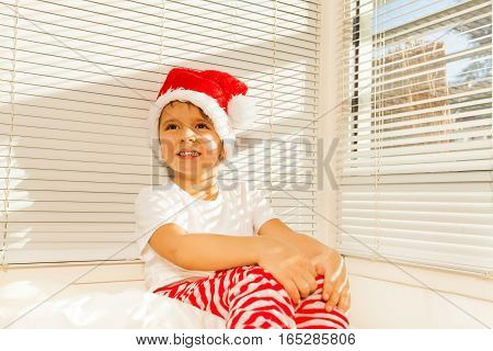 Portrait of happy boy in Santa's costume dreaming sitting on his bed in holiday morning