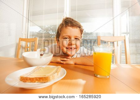 Portrait of happy six years old boy sitting at a table with orange juice, sandwich and cereals in the kitchen