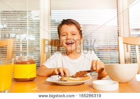 Portrait of smiling boy spreading chocolate with a knife on his toast sitting at a table in the kitchen