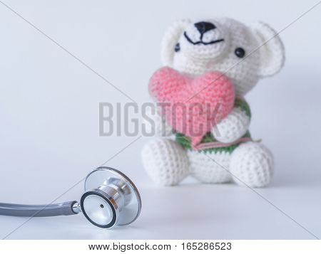 Stethoscope And Teddy Bear Holding A Heart On White Background. Health Care Of Kids , Concept.