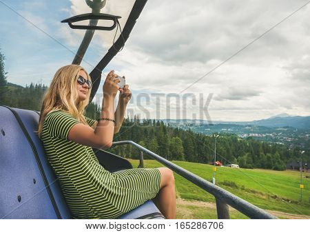 Young blond woman tourist making photoes with smartphone on a cable car in Zakopane, Mountain region and natural resort in Poland