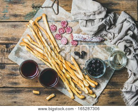 Wine and appetizers set. Italian Grissini bread sticks, dry cured pork meat sausage, black olives in jar and red wine in glasses on rustic wooden background, top view
