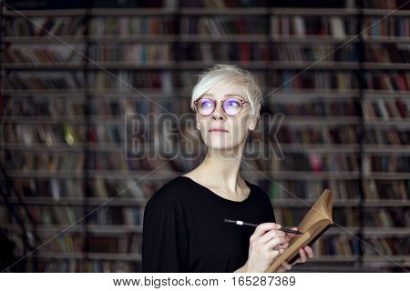 Portrait of woman with blonde hair and eyeglasses in a library opened book. Hipster student. Education concept