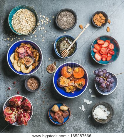 Ingredients for healthy breakfast over grey stone background, top view, square crop. Fresh and dried fruit, chia seeds, oatmeal, nuts, honey. Clean eating, vegan, healthy food, detox, dieting concept