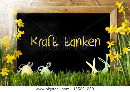 Blackboard With German Text Kraft Tanken Means Relax. Sunny Spring Flowers Nacissus Or Daffodil With Grass, Easter Egg And Bunny. Rustic Aged Wooden Background.